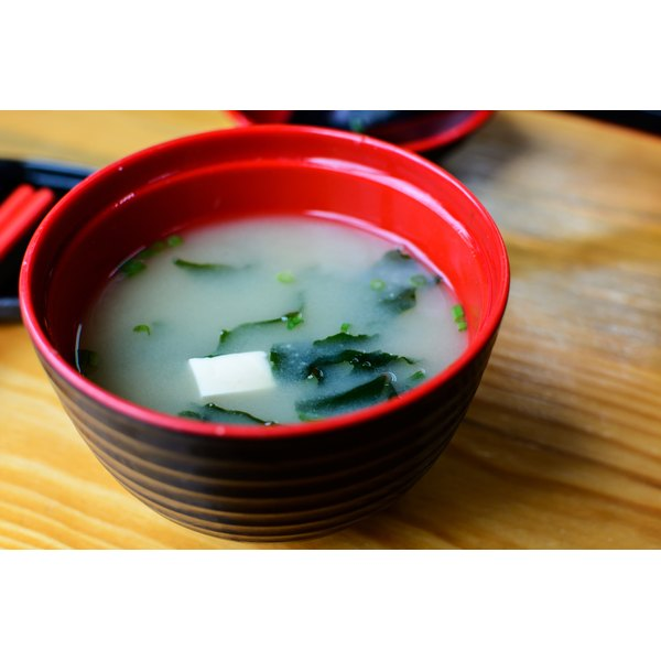 A bowl of miso soup on a table.