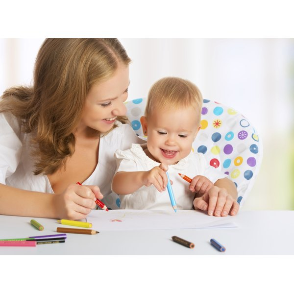 A young baby with his his mother holds a colored pencil.