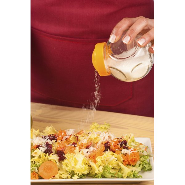 Woman adding salt to her dinner.