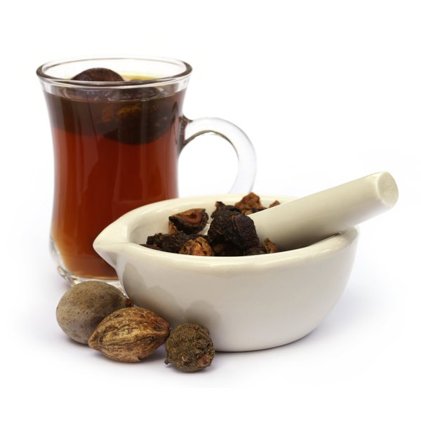 Triphala in a mortar and pestle and a glass of triphala tea.