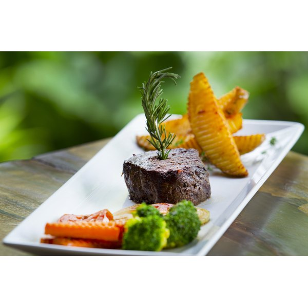 A beef filet served with potato wedges, vegetables and a sprig of rosemary.