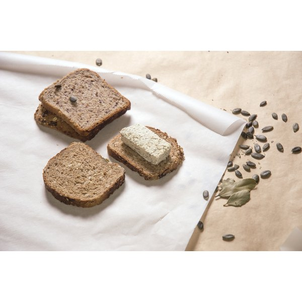 Multiple pieces of pumpernickel bread on a piece of paper.