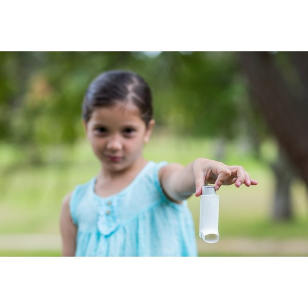 A young girl is holding an inhaler.