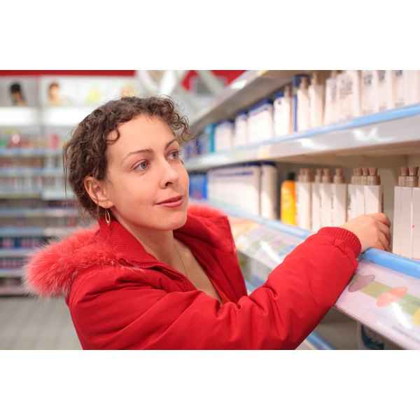 A woman shopping for moisturizer in a drug store.