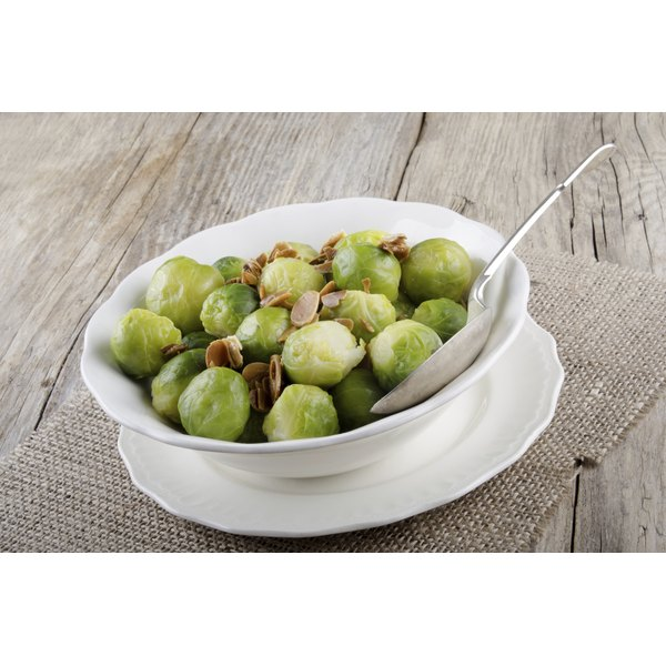 A small bowl of brussels sprouts with slivered almonds on top.