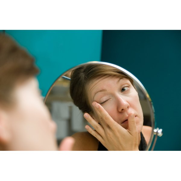 A woman looking in a mirror while applying eye cream.