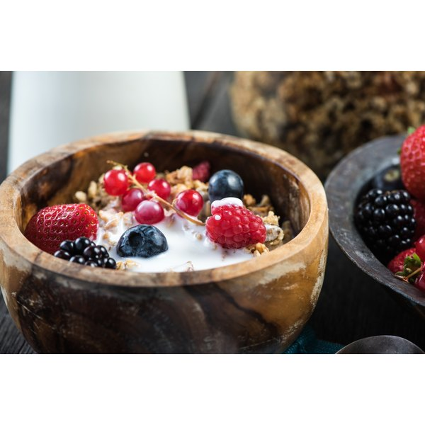 A bowl of granola with yogurt and berries.