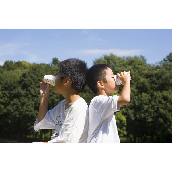 Two boys drinking from cups