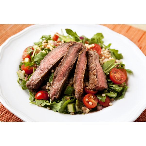 A salad tossed with pearl couscous and topped with slices of tri-tip.