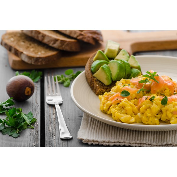 Scrambled eggs topped with salmon served with whole grain toast and avocado.