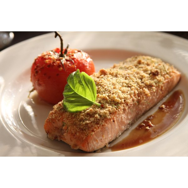 Roasted almond crusted salmon with a tomato on a plate.