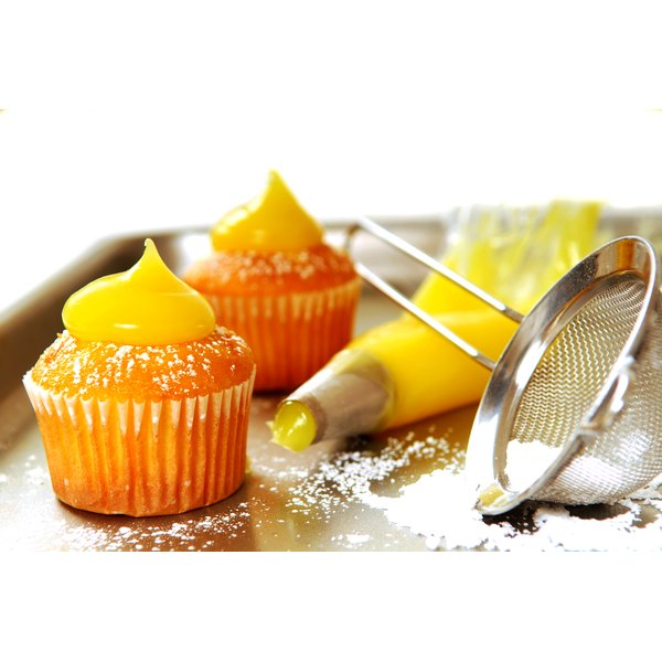 Lemon curd filled cupcakes with a sprinkle of powdered sugar and a dollap of lemon curd on top.