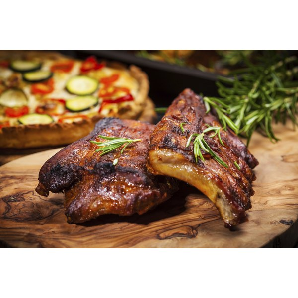 A juicy spare ribs with herbs, on a wooden cutting board.