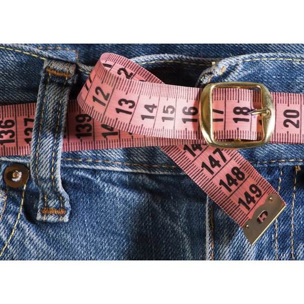 Close up of a waist with a tape measure being used as a belt.