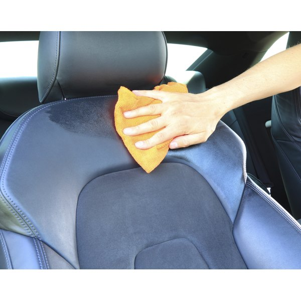 A woman is cleaning leather in her car.