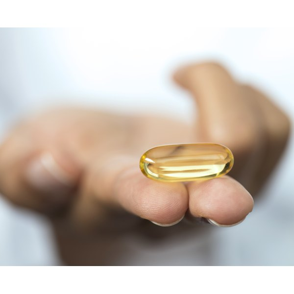A close-up of a hand holding a fish oil supplement.