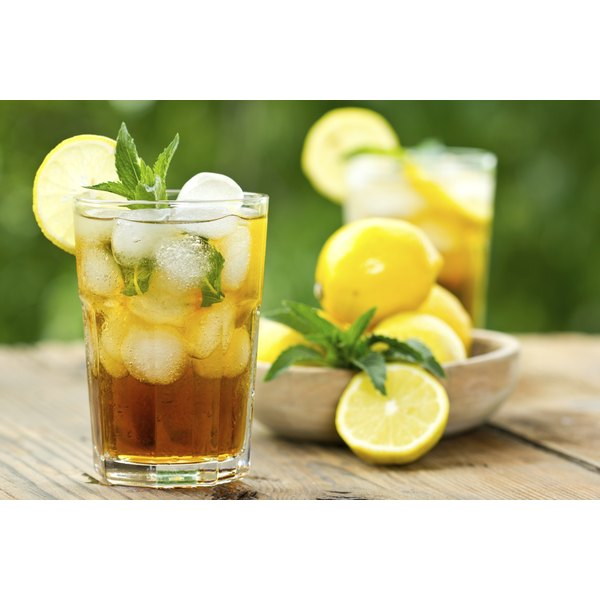 A glass of ice tea with lemons and limes.