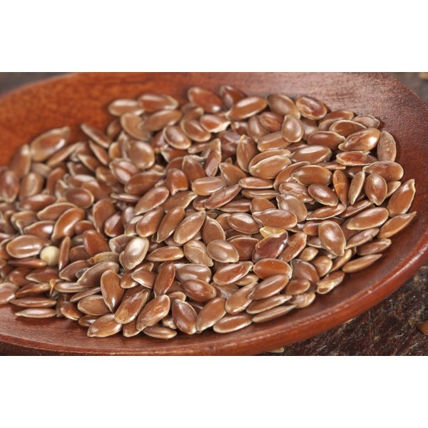A close-up of flaxseeds in a wooden bowl.