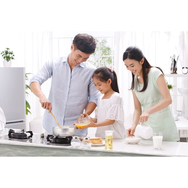 A family is cooking in their kitchen.