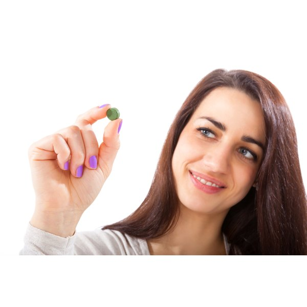 A woman is holding a pill in her hands.