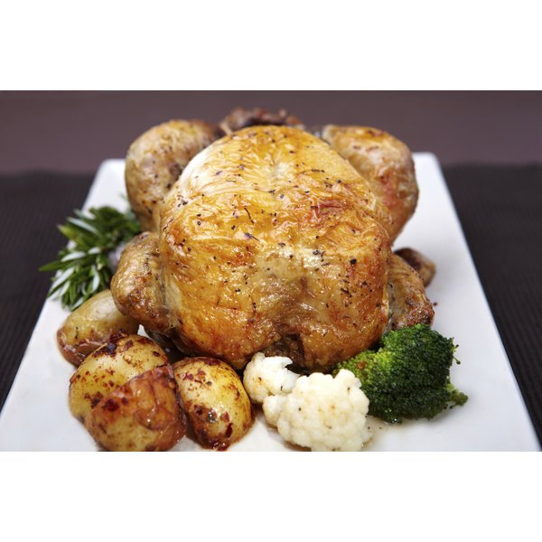 A whole smoked chicken sits on a square white serving dish surronded by roasted vegetables.