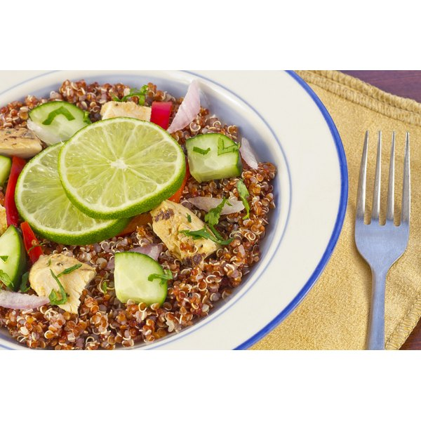 A bowl of quinoa topped with grilled chicken pieces.
