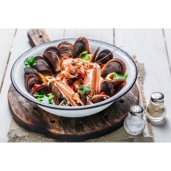 An assortment of shellfish sit in a pot on a rustic table.
