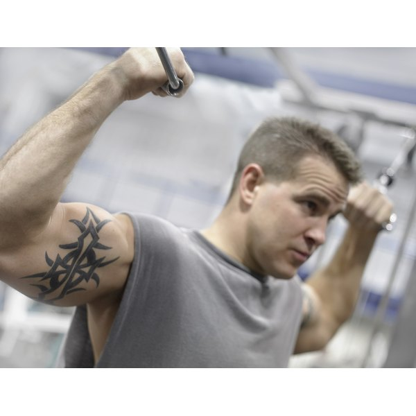 Muscular man working out his arms at the gym