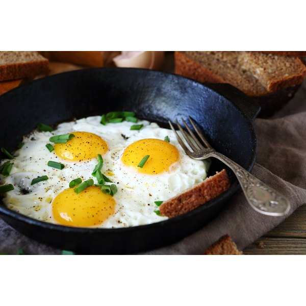 Fried eggs with scallions in a pan.