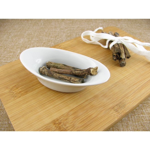 Licorice root sticks in a bowl on a wooden cutting board.