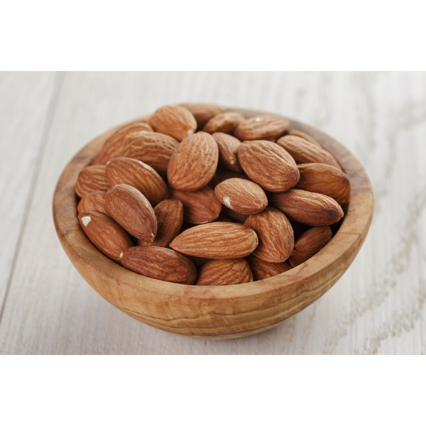 A bowl of roasted almonds on a wooden table.