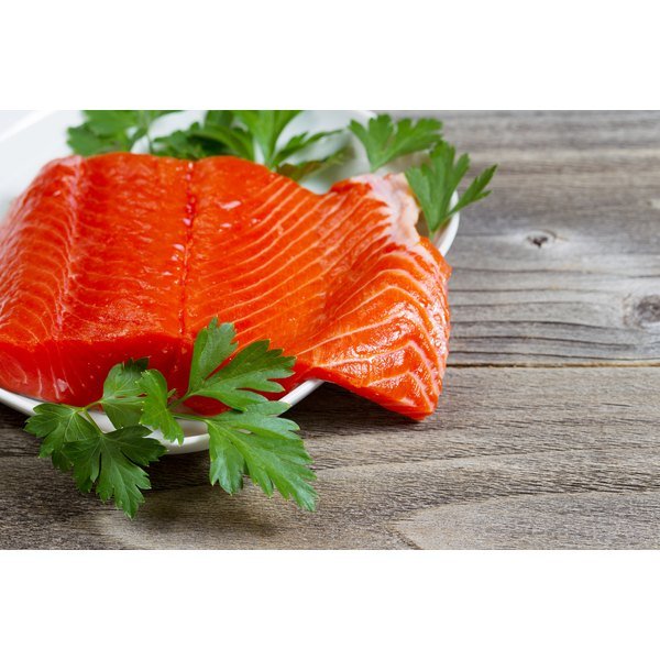 A raw salmon fillet on a wooden cutting board.