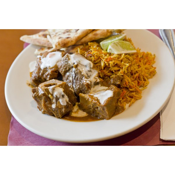 A plate of goat stew served with basmati rice and naan bread.