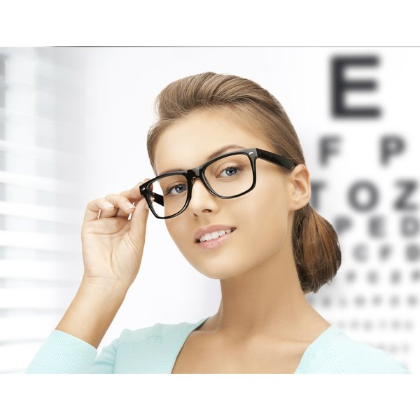 Young adult woman with glasses stands in front of a vision chart