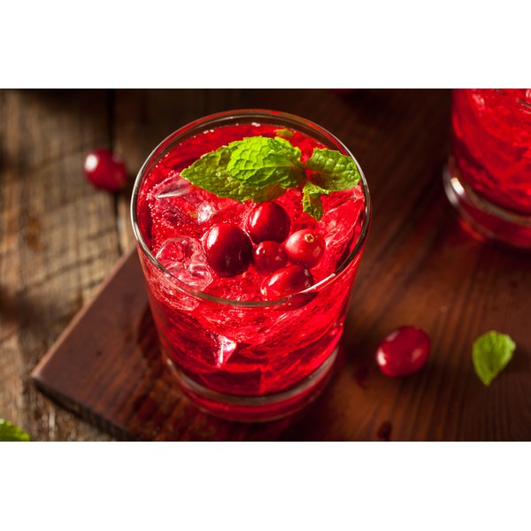A glass of fresh cranberry juice with mint leaves on top.