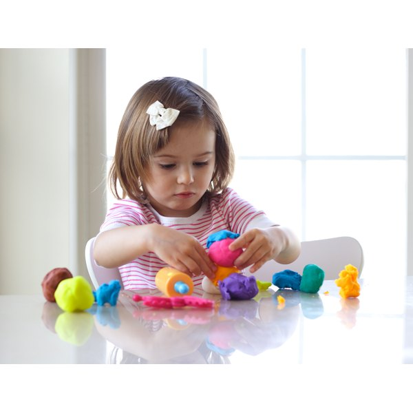 A 2-year-old girl creating colorful forms with modeling clay.