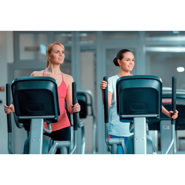 Two women are using elliptical machines.