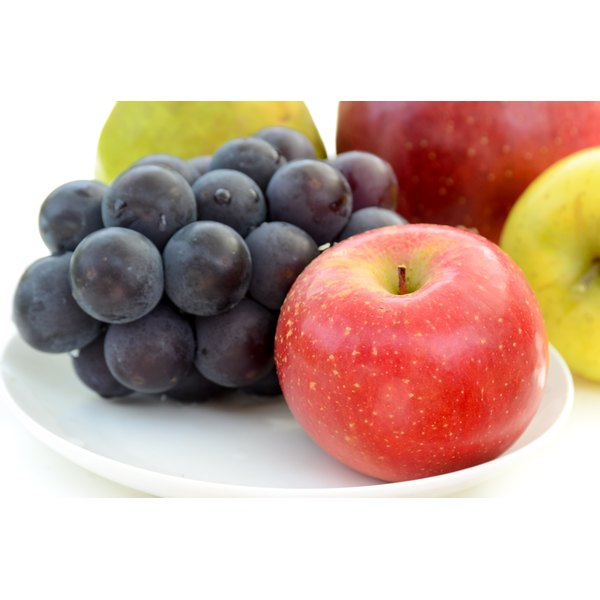 Grapes and apples on a white plate.