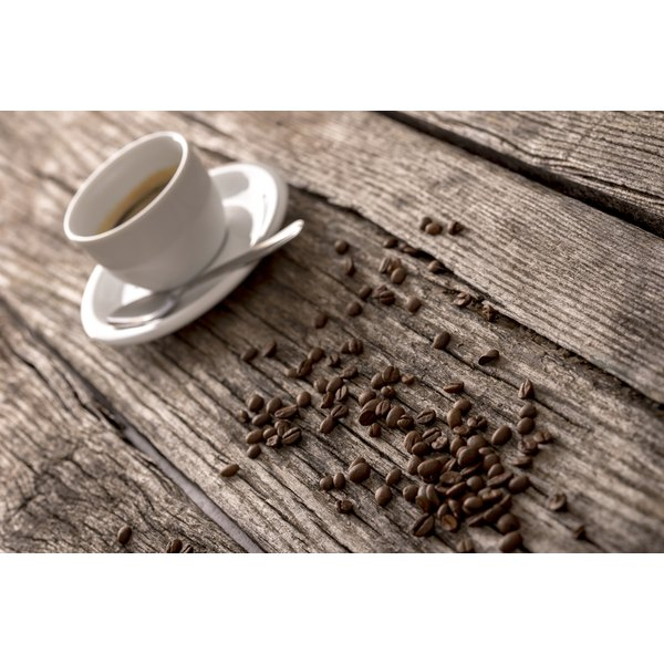 A cup of coffee with coffee beans on a wooden table.