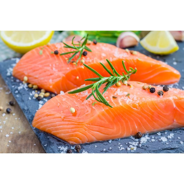 Two salmon fillets on a board.