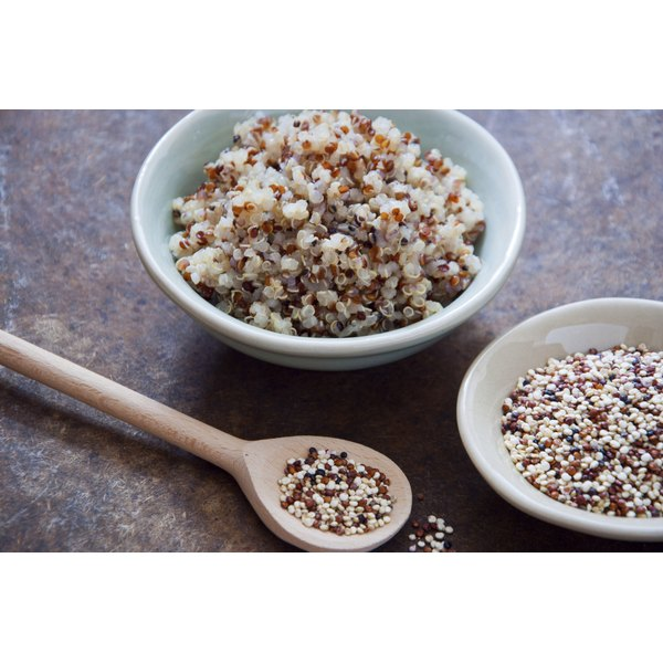 A bowl of cooked and raw quinoa next to a wooden spoon of quinoa.