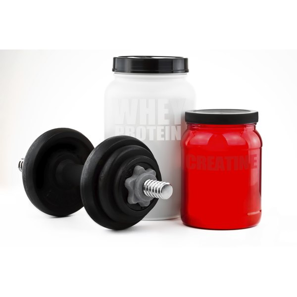 Two jugs of protein powder and a dumbbell.