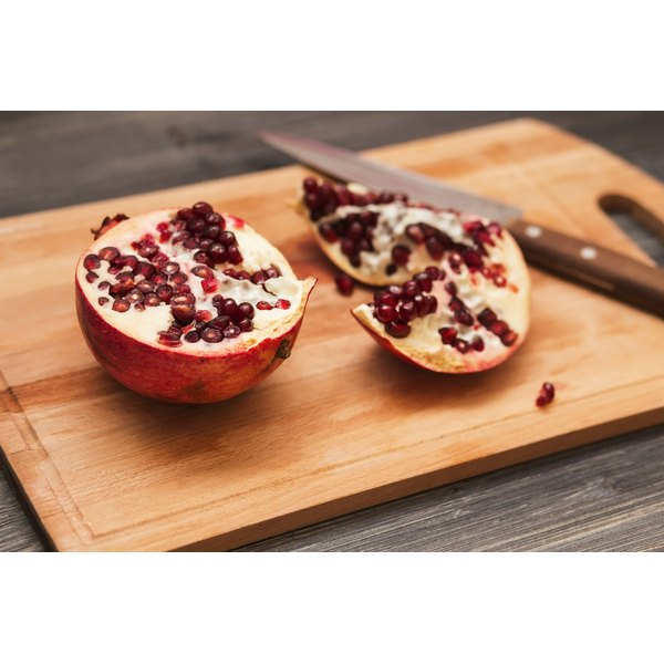A cut up pomegranate on a wooden cutting board.