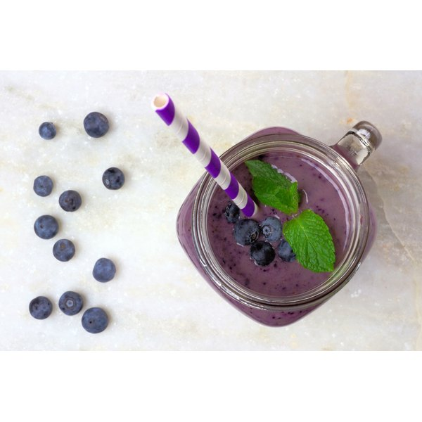 A blueberry smoothie with a striped straw.
