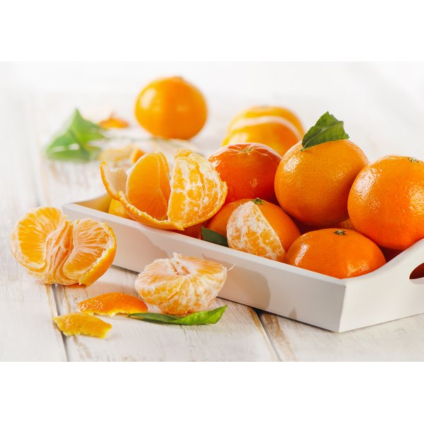 A small crate filled with tangerines.