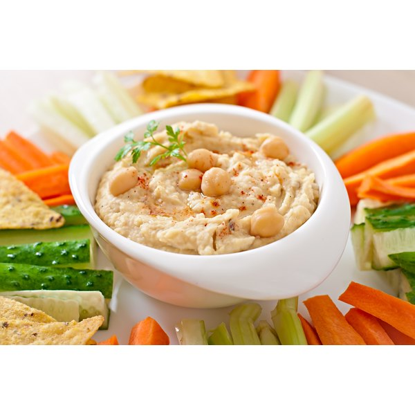 A bowl of hummus surrounded by fresh vegetables.