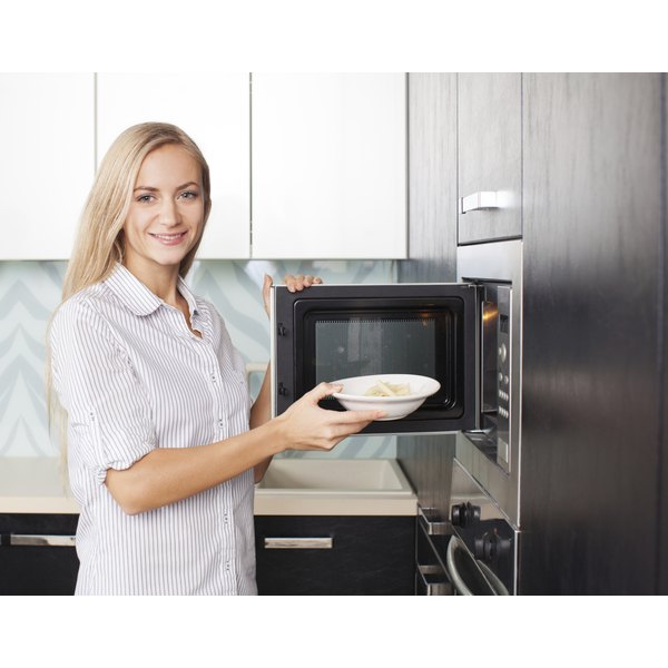 A woman is pulling food out of a microwave.