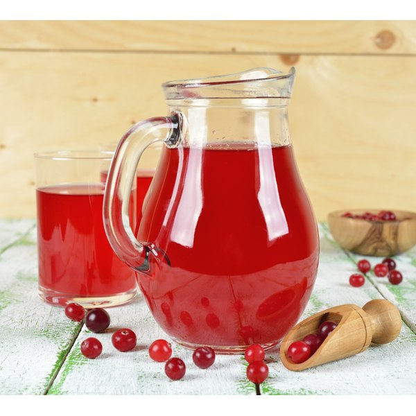 A tall pitcher of cranberry juice beside a glass of cranberry juice.