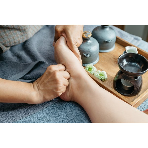A reflexologist pressing into the sole of a woman's foot.