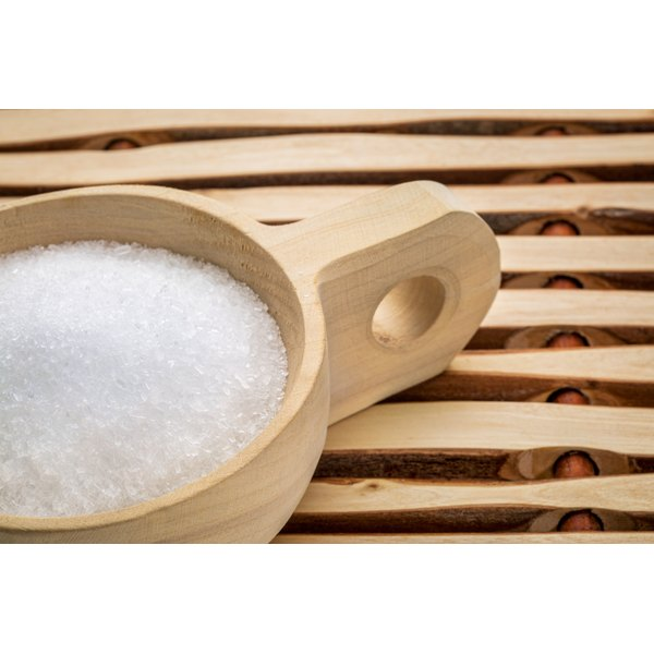 Epsom salts sit in a wooden cup on a bathmat made of wooden slats.